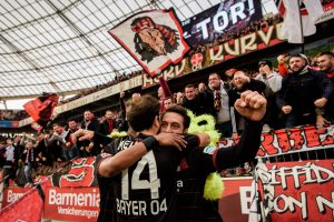 Bayer 04 Leverkusen's Admir Mehmedi and Hakan Calhanoglu (10) celebrate with fans a 1-0 Bundesliga league game victory over SV Darmstadt 98 in May 2016. (Photo: Joerg Schueler